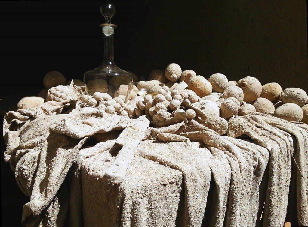 Una tavola imbandita richiama una scena di vita quotidiana fatta di oggetti significanti.