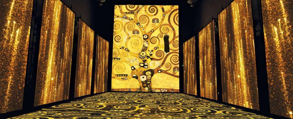 Le proiezioni interagiscono con l'ambiente che le ospita, ridisegnandolo e valorizzandolo. I motivi tratti dai dipinti più celebri del grande artista rivestono lo spazio e avvolgono lo spettatore. Particolare e texture ispirate a G. Klimt, L'albero della vita, dal Fregio per Palazzo Stoclet a Bruxelles.