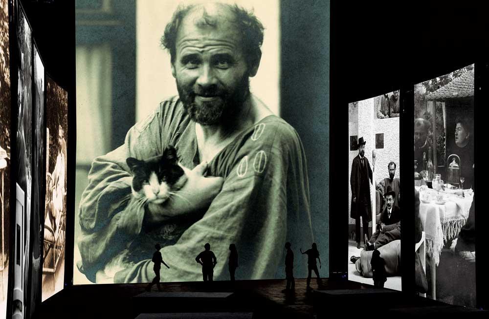 Nello schermo centrale una fotografia di Gustav Klimt che bene rappresenta il carattere eccentrico dell'artista. Sugli schermi laterali foto di gruppo dei secessionisti viennesi.